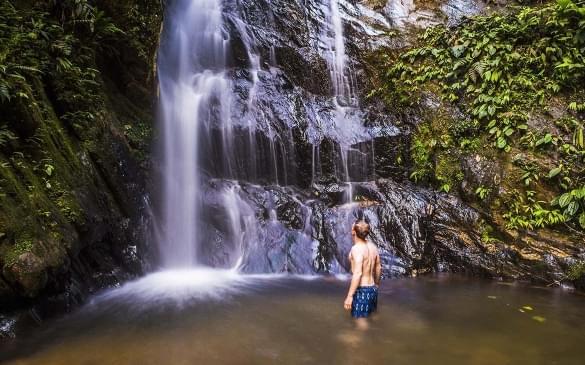 Tourist under Cucharillos Waterfall in the Mashpi Cloud Forest area of the Choco Rainforest, Pichincha Province, Ecuador, South America