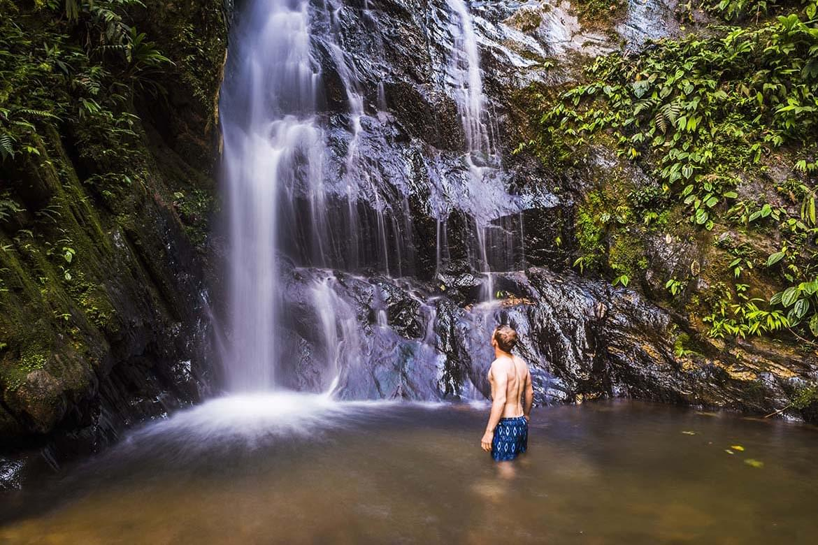 Tourist under Cucharillos Waterfall in the Mashpi Cloud Forest area of the Choco Rainforest, Pichincha Province, Ecuador, South America